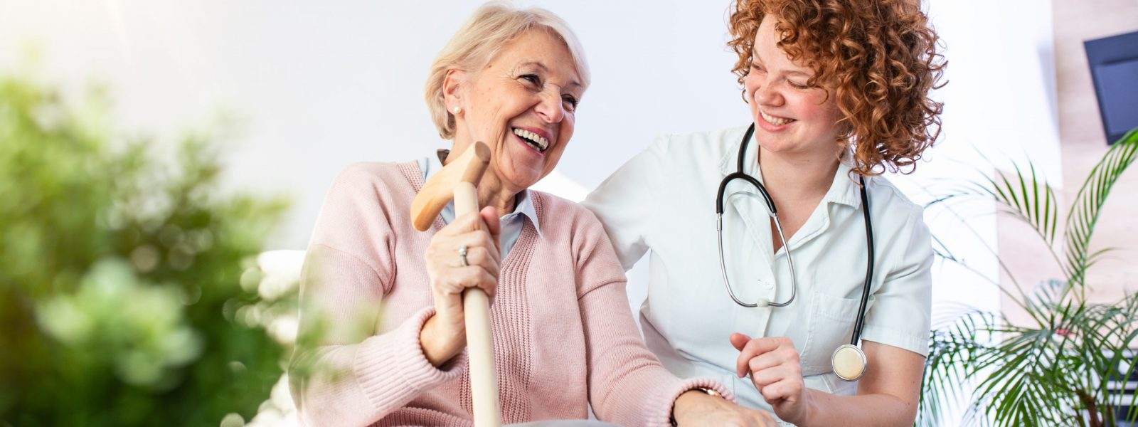 Friendly relationship between smiling caregiver in uniform and happy elderly woman. Supportive young nurse looking at senior woman. Young caring lovely caregiver and happy ward